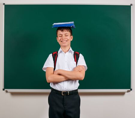 Portrait of a school boy posing with backpack and school supplies, blackboard background - back to school and education concept Standard-Bild