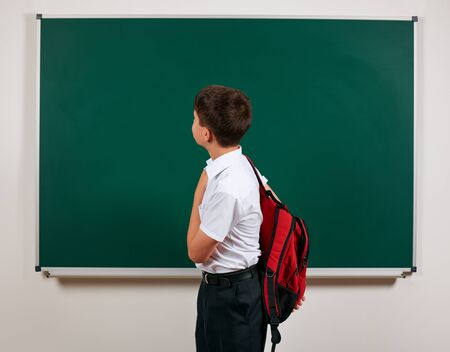 Portrait of a school boy posing with backpack on blackboard background - back to school and education concept 免版税图像