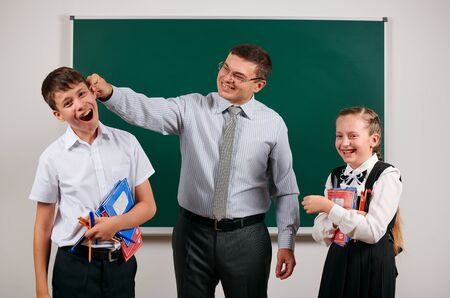 Portrait of a teacher grabs schoolboys ear, who has bad discipline, and happy schoolgirl. Posing with exercise books, pens, pencils and other school supplies on blackboard background Фото со стока