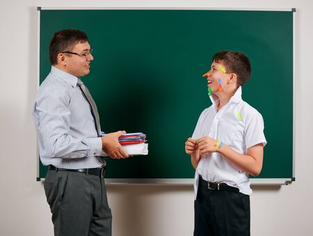 Portrait of a teacher and funny schoolboy with low discipline, poor school performance, posing at blackboard background - back to school and education concept