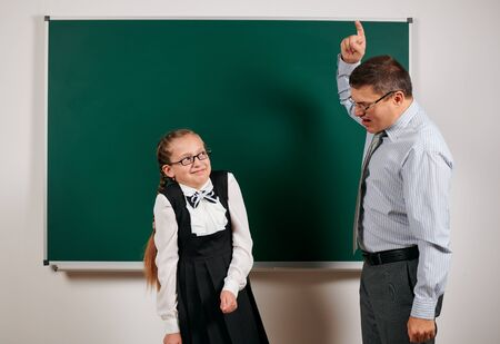 angry teacher shout to schoolgirl, posing at blackboard background - back to school and education concept