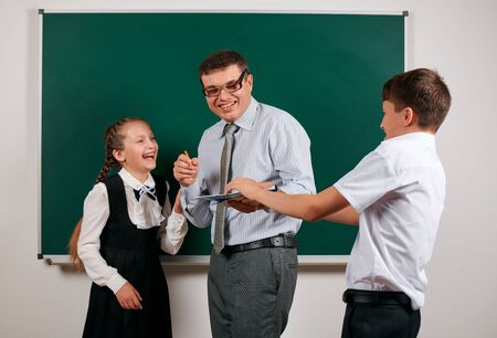 Portrait of a teacher checking homework, reading school exercise books, schoolboy and schoolgirl with old fashioned eyeglasses posing on blackboard background - back to school and education concept