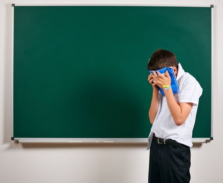 Portrait of funny pupil. School boy very emotional, having fun and very happy, blackboard background - back to school and education concept