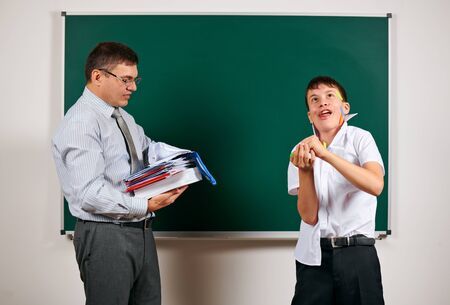 Portrait of a teacher and funny schoolboy with low discipline. Pupil very emotional, having fun and very happy, posing at blackboard background - back to school and education concept