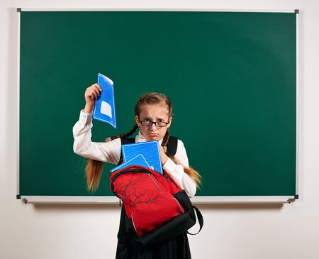 Portrait of a schoolgirl with backpack and school supplies near blackboard background - back to school and education concept
