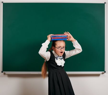 Portrait of a very emotional schoolgirl, pupil playing with workbooks and school supplies near blackboard background - back to school and education concept Banque d'images