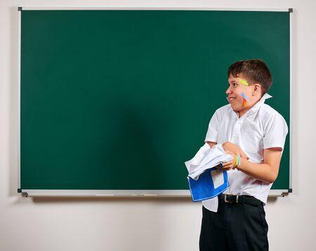 Portrait d'élève drôle. Écolier très émotif, s'amusant et très heureux, fond de tableau noir - concept de retour à l'école et à l'éducation