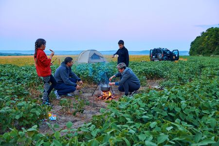 Family traveling and camping, twilight, cooking on the fire. Beautiful nature - field, forest and moon. Stockfoto