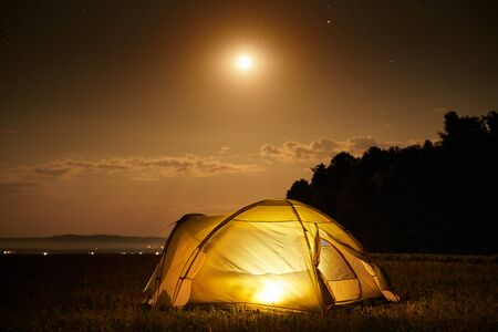 Traveling and camping concept - camp tent at night under a sky full of stars. Orange illuminated tent. Beautiful nature - field, forest, plain. Moon and moonlight
