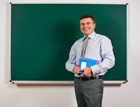Portrait of a man as a teacher, posing at school board background - learning and education concept