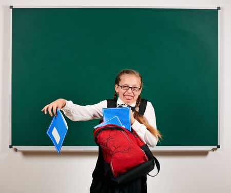 Portrait of a schoolgirl playing with backpack and school supplies near blackboard background - back to school and education concept