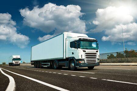 Weißer LKW ist auf der Autobahn - Geschäfts-, Handels-, Frachttransportkonzept, klarer und leerer Raum in der Seitenansicht Standard-Bild