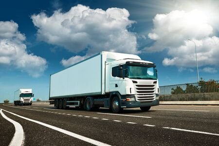 White truck is on highway - business, commercial, cargo transportation concept, clear and blank space on the side view Stock Photo