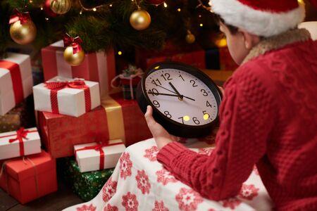 Teen boy waitnig for Santa and watching the clock, lying indoor near decorated xmas tree with lights, dressed as Santa helper - Merry Christmas and Happy Holidays! 版權商用圖片