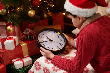 Teen boy waiting for Santa and watching the clock, lying indoor near decorated xmas tree with lights, dressed as Santa helper - Merry Christmas and Happy Holidays! 版權商用圖片