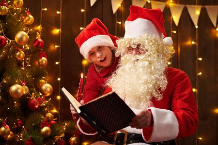 Santa Claus and santa helper boy reading book, sitting indoor near decorated xmas tree with lights - Merry Christmas and Happy Holidays! 写真素材