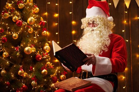 Santa Claus reading book, sitting indoor near decorated xmas tree with lights - Merry Christmas and Happy Holidays! 写真素材