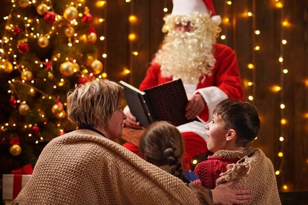 Santa Claus reading book for family. Mother and children sitting indoor near decorated xmas tree with lights - Merry Christmas and Happy Holidays! 写真素材