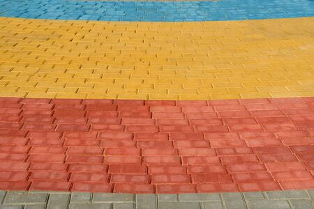 yellow, red and blue paving tiles for background or texture Stockfoto