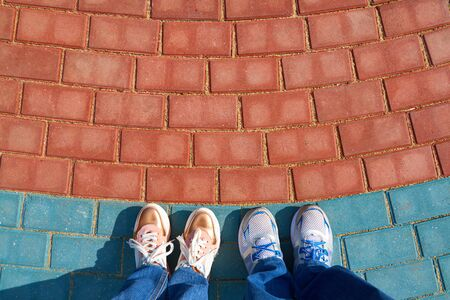 human foots in shoes standing on the pavement tiles Stockfoto