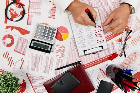 Flat top view of businessman working and calculating finance, reads and writes reports. Business financial accounting concept.