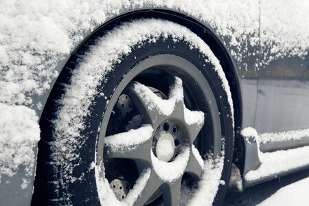 Cars tyre covered by snow on street in winter day