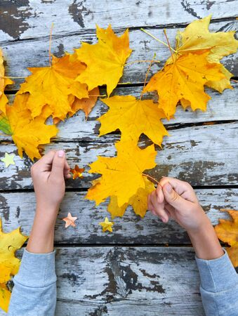 Hands with Autumn Leaves over wooden background