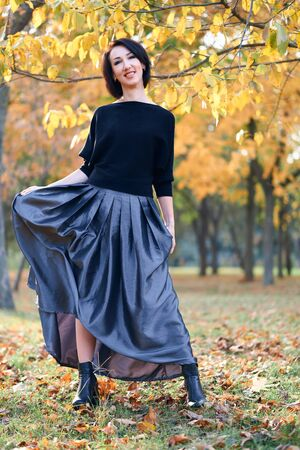 Beautiful elegant woman standing and posing in a city park in autumn