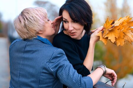 Two girlfriends talking and posing in autumn city park. Beautiful adult woman, blond and brunette.