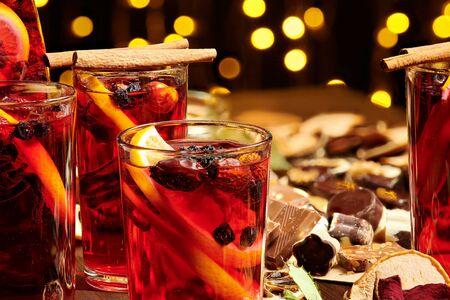 Świąteczne grzane wino lub gluhwein z przyprawami, czekoladowymi słodyczami i plasterkami pomarańczy na rustykalnym stole, tradycyjny napój na ferie zimowe, lampki choinkowe i dekoracje