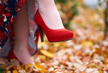close up of womens feet shod in red high heels shoes, autumn season, yellow fallen leaves as background