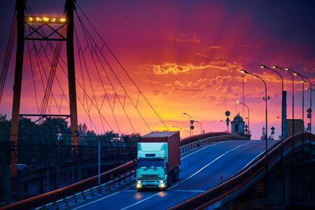 ciężarówka z kontenerem przejeżdża przez most, piękny zachód słońca, wagony towarowe w przemysłowym porcie morskim, droga idzie w górę