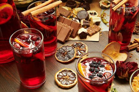 Christmas mulled wine or gluhwein with spices, chocolate candies, sweets and orange slices on rustic table, traditional drink on winter holiday, christmas lights and decorations