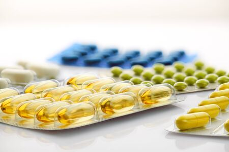 Various tablets, pills and vitamins in blister pack on white background. Global healthcare concept. Antibiotics drug resistance. Antimicrobial capsule pills. Pharmaceutical industry. Pharmacy.