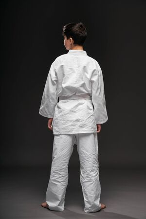 backside view of a teenager dressed in martial arts clothing poses on a dark gray background, a sports concept