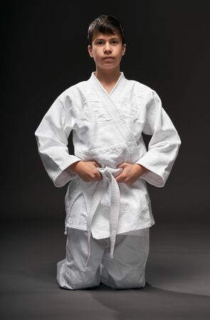 sport concept - a teenager dressed in martial arts clothing poses on a dark gray background, studio shoot