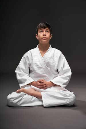 a teenager dressed in martial arts clothing poses on a dark gray background, a sports concept