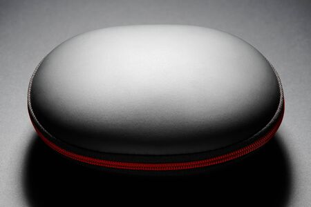 black hard bag in a shell form with red zipper on dark background