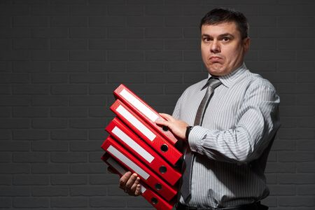 Very busy businessman closeup portrait, posing with red folders, overworking concept, dark wall background