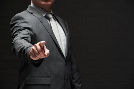 businessman portrait pointing by forefinger, dressed in gray suit, dark wall background Reklamní fotografie