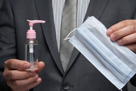 a man demonstrates a protective face mask for antivirus individual protection and bottle of sanitizer liquid- healthcare and medicine concept, prevention tips Stock Photo
