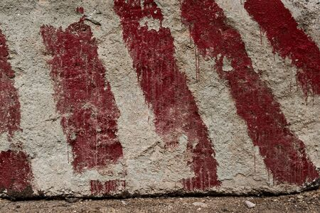 red stripes painted on the concrete as a warning and an indication of the size and limits as background or texture