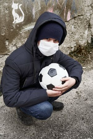 concept of epidemic and quarantine - a boy with a face mask and a ball alone on the street in the city