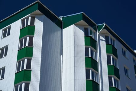 facade of a new multistory building with white and green metal siding, many Windows