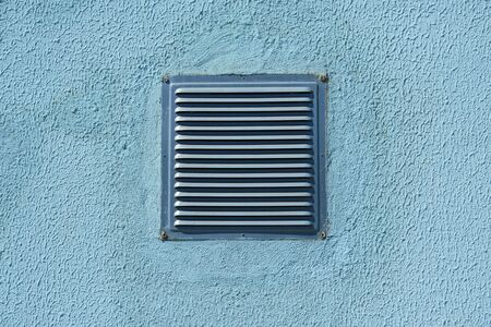 square metal ventilation grate in a blue wall, close view, delivers fresh air and cools Banque d'images