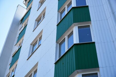facade of a new multi-storey building with white and green metal siding, many Windows Imagens