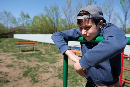 Unhappy teen portrait, he stands by the outdoor workout equipment and thinks