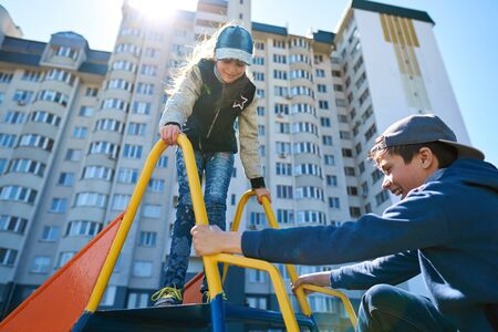 Children play on the playground next to a condominium. Swing, slide, stairs, multistory building. A place for children to play. Urban residential infrastructure.