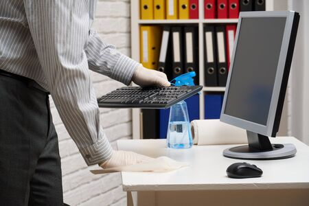 concept of cleaning or disinfecting the office - a businessman cleans the workplace, computer, desk, uses a spray gun and paper napkins. Cleaning surfaces from microbes, viruses and dirt. Foto de archivo