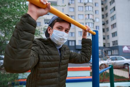 teen boy stands near horizontal bar of outdoor workout equipment, on playground near high-rise buildings with apartments, a medical mask on his face protects against viruses and dust